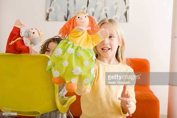 Girl (8-9) and boy (6-7) playing with glove puppets