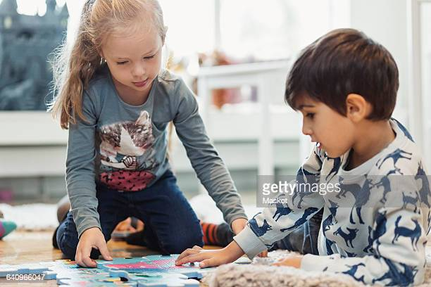 Girl and boy playing with jigsaw pieces