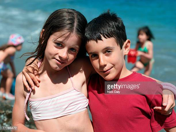 girl and boy posing together at beach - kids swimsuit models stock pictures, royalty-free photos & images