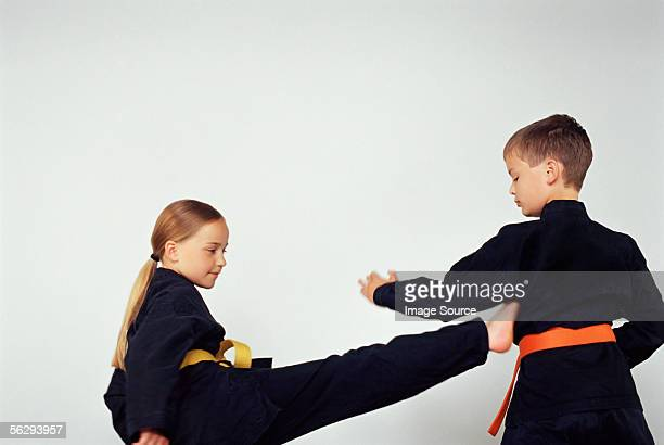 girl and boy practicing karate - girl fight stock photos and pictures