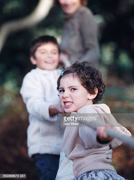 Girl (5-7) and boy (9-11) pulling on rope outdoors