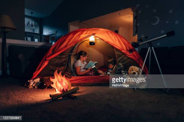 girl and boy reading while camping indoors - tent stock pictures, royalty-free photos & images