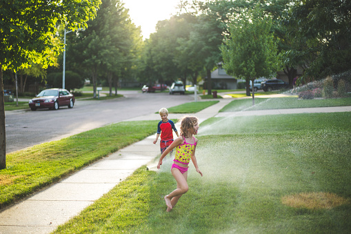 Girl and Boy running Through Sprinkler - gettyimageskorea