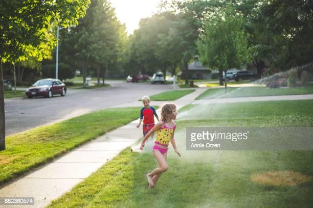 Girl and Boy running Through Sprinkler