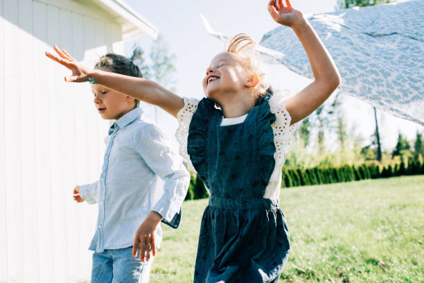 girl and boy running through the washing on the line with great joy