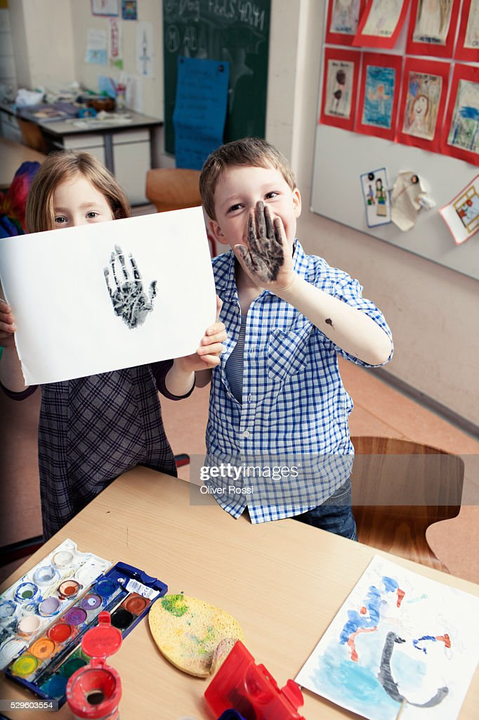 Girl (6-7) and boy (6-7) showing hand print during art class : Stock-Foto