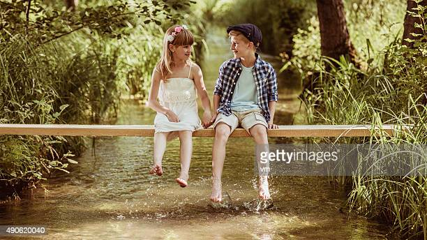 Girl and boy sitting above stream talking and holding hands