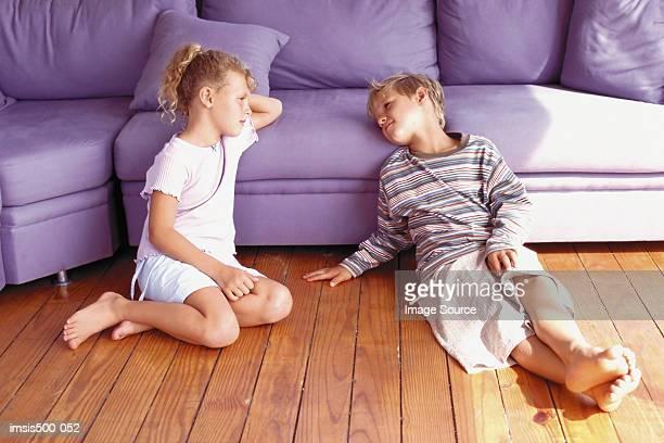 Girl and boy sitting against sofa