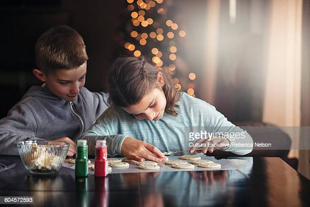 Girl and boy sitting at table decorating christmas cookies