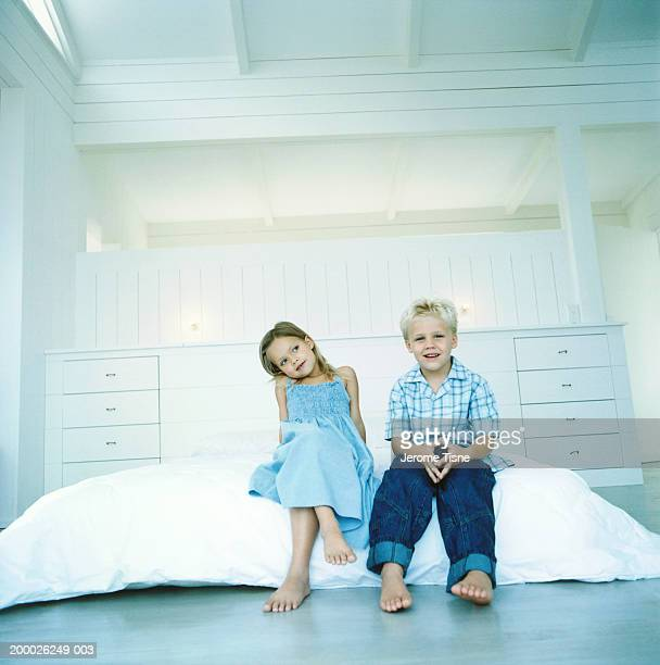 Girl and boy (4-6) sitting beside each other on bed