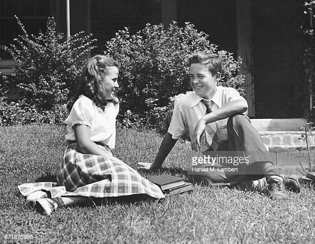 girl and boy sitting in garden and talking - {{ contactusnotification.cta }} stockfoto's en -beelden