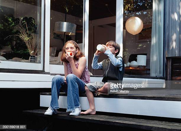 Girl and boy (6-10) sitting on porch steps, eating and drinking