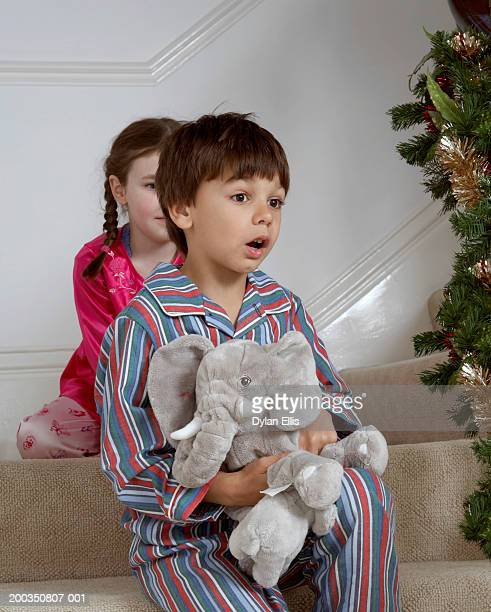 Girl and boy (5-7) sitting on stairs, boy holding soft toy, mouth open