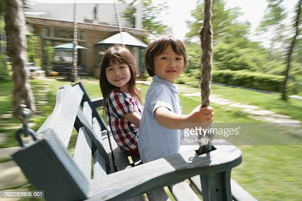 Girl and boy (4-7) sitting on swing, portrait (blurred motion)