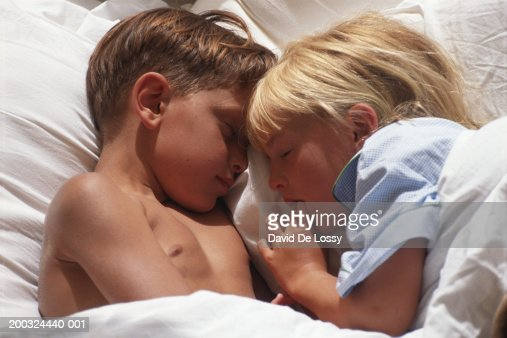 Girl And Boy Sleeping On Bed Elevated View Stock Photo -5896