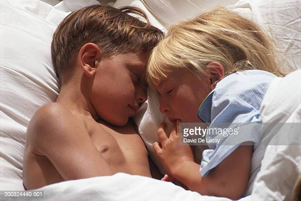 Girl and boy (6-9) sleeping on bed, elevated view