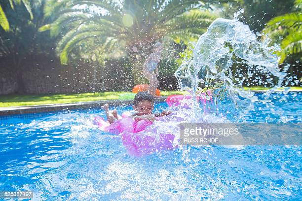 Girl and boy splashing around in garden swimming pool