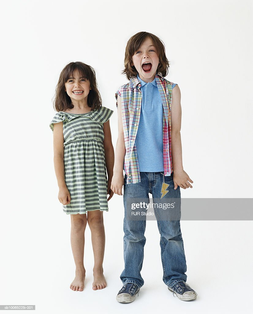 Girl (6-7) and boy (8-9) standing against white background, portrait : Stockfoto