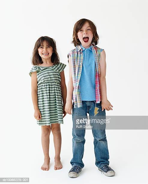 Girl (6-7) and boy (8-9) standing against white background, portrait