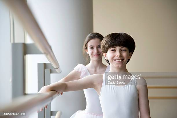 Girl and boy (12-14) standing at bar in ballet class, smiling