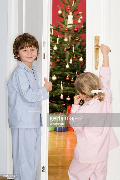 Girl and boy standing at door watching Christmas tree