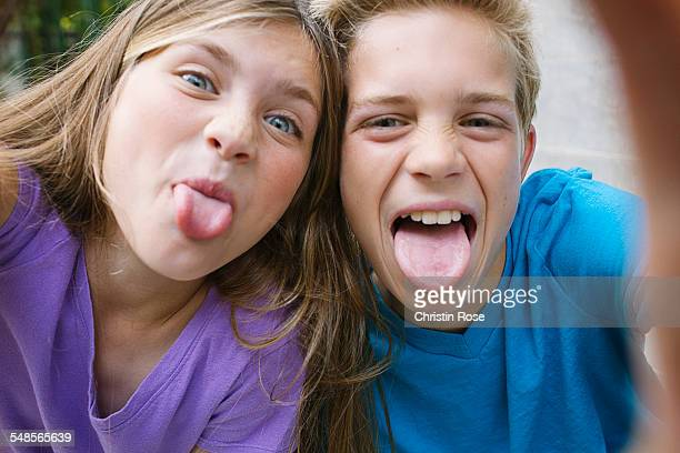 Girl and boy sticking out tongues