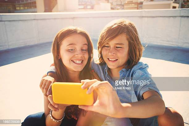 Girl and Boy (8 -10) taking self-portrait