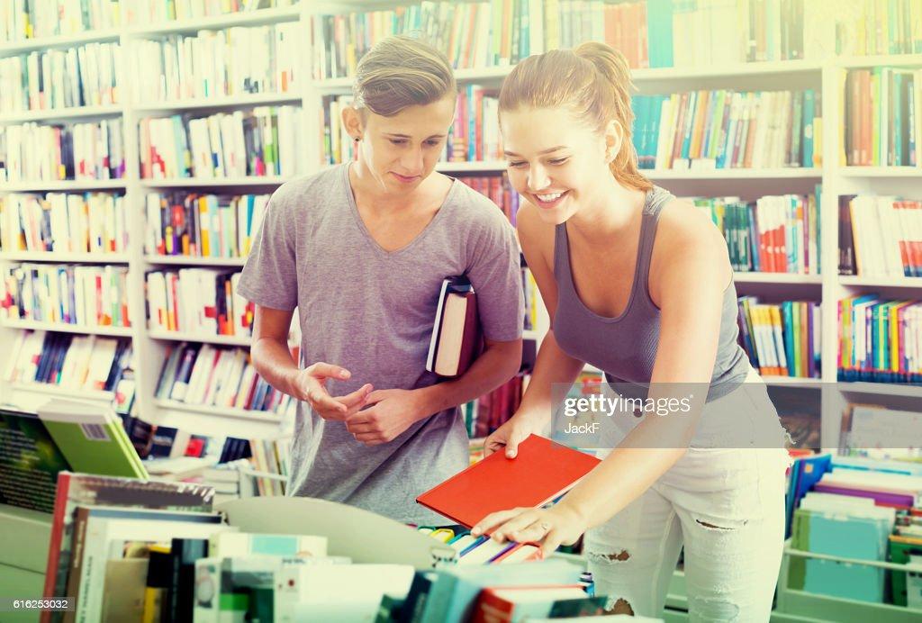 girl and boy teenagers in book store : Foto de stock
