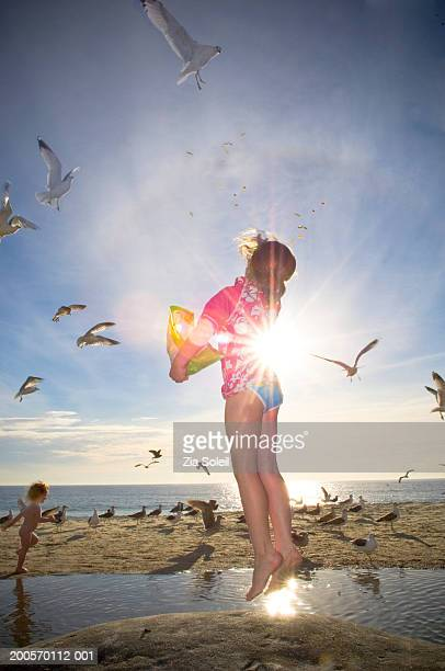 Girl and boy (2-7) throwing food in air for seagull at beach