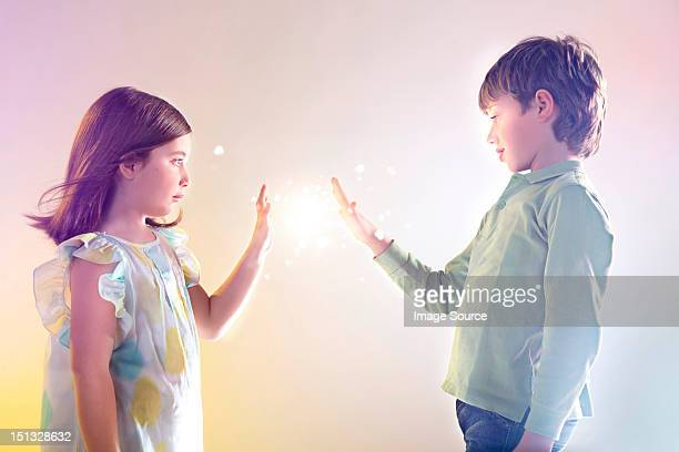 Girl and boy touching bright lights