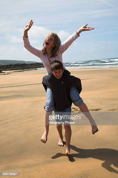 girl and boy twins with brother giving her sister a piggyback ride on the beach