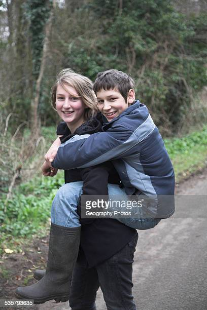 girl and boy twins with sister giving her brother a piggyback ride