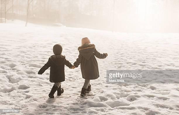 Girl and boy walking in winter scene