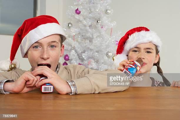 Girl and boy wearing Santa hats eating Santa Claus chocolates