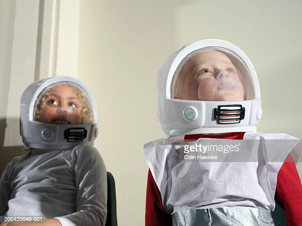 Girl and boy (5-7) wearing spacemen costumes, looking up, close-up