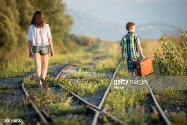 mädchen und junge mit tasche zu fuß auf denkgleisen - kemter stock-fotos und bilder