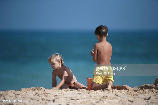 Girl and boy (6-9) with bucket on beach