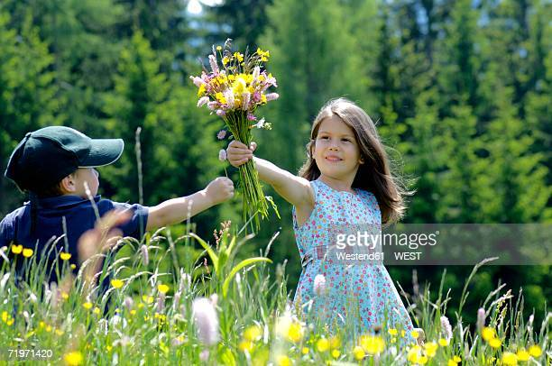 Girl and boy (3-7) with bunch of flowers in meadow