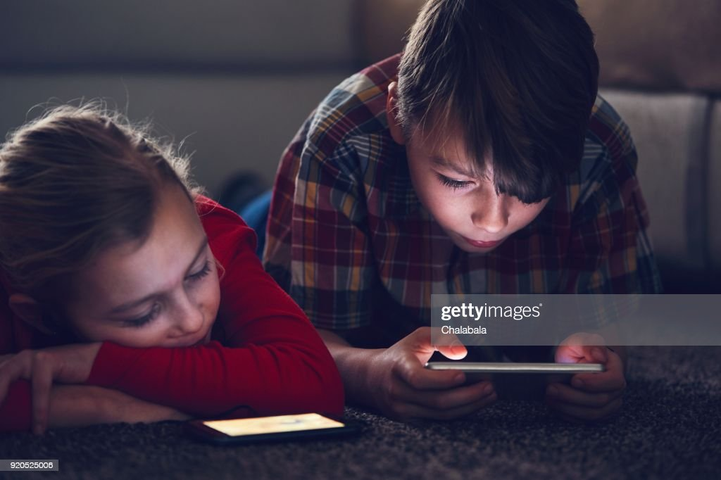 Girl and boy with their smart phones : Stock Photo