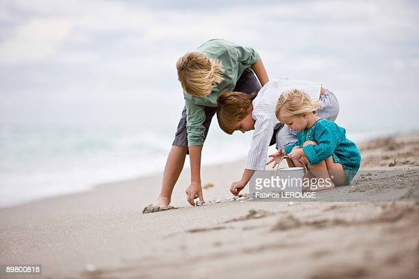 Girl and boys playing with shells on the beach