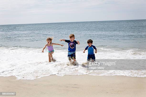 girl and boys running and slashing in sea - cape may stock pictures, royalty-free photos & images