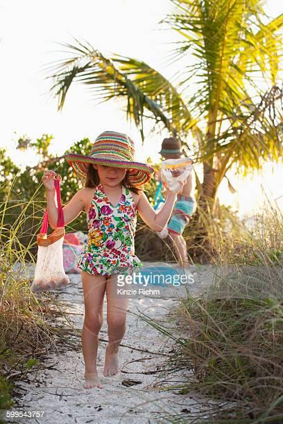 Girl and brother collecting seashells at beach, Sanibel, Florida, USA