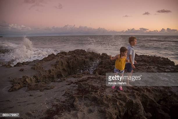 girl and brother looking out from beach at sunrise, blowing rocks preserve, jupiter island, florida, usa - jupiter island florida stock photos and pictures