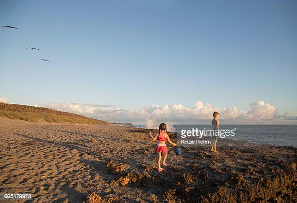 Girl and brother playing on beach, Blowing Rocks Preserve, Jupiter Island, Florida, USA