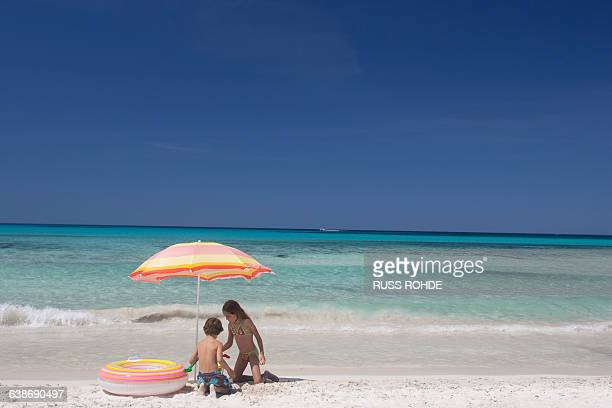 Girl and brother playing under beach umbrella on beach, Majorca, Spain