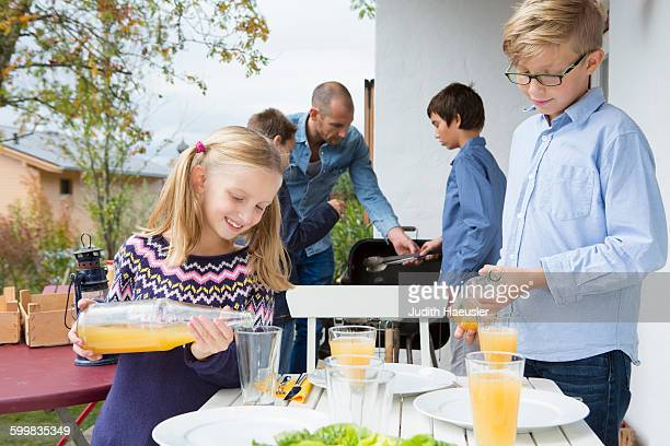 Girl and brother pouring juice at garden barbecue table