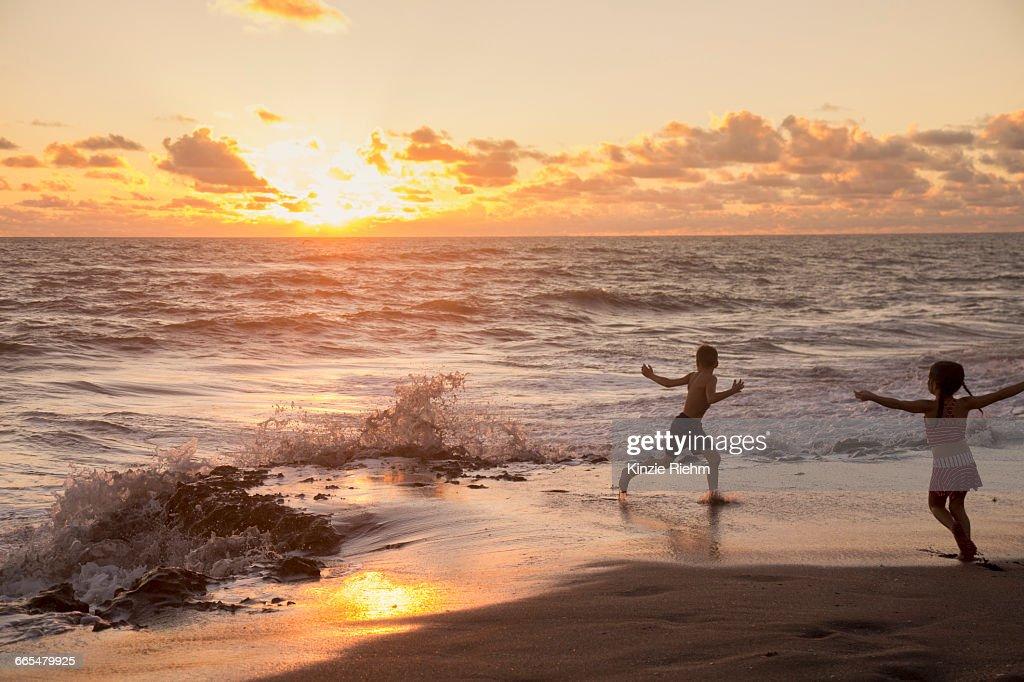 Girl and brother running on beach at sunrise, Blowing Rocks Preserve, Jupiter Island, Florida, USA : Stock Photo