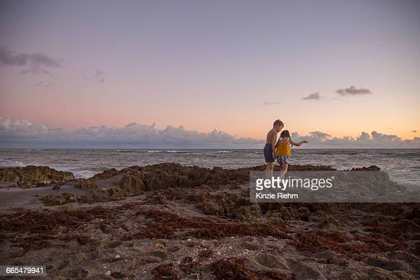 girl and brother stepping over beach rocks at sunrise, blowing rocks preserve, jupiter island, florida, usa - blowing rocks preserve stock photos and pictures