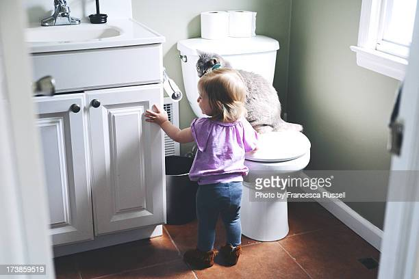 Girl and cat in bathroom.