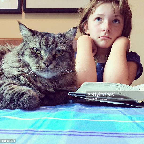 Girl and Cat Looking up from Book